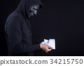 Mystery man holding and looking at white mask 34215750