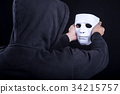Mystery man holding and looking at white mask 34215757