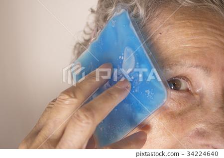 Senior woman with ice on head for headache 34224640