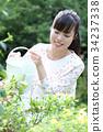 꽃에 물을하는 여성 34237338