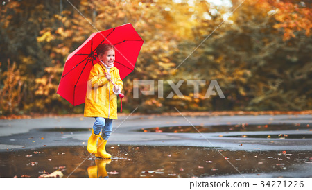 happy child girl with an umbrella and rubber boots in puddle  on 34271226