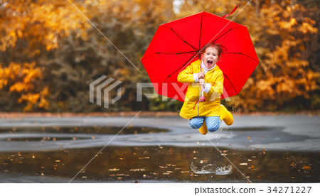 happy child girl with an umbrella and rubber boots in puddle  on 34271227