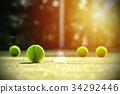 Tennis balls on grass court with sunlight 34292446