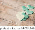 Green pastel hearts on textured wooden table 34295346