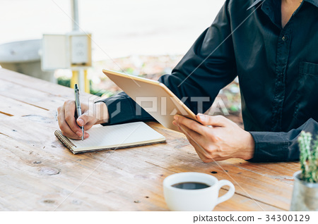 Business man hand holding tablet and writing  34300129