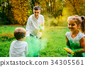 father doughet and son playing with holi paints 34305561