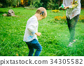 Boy with hearing aid playing with holi paints 34305582