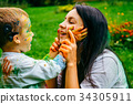 Happy mother and son playing with holi paints 34305911