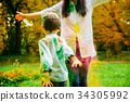 Happy mother and son playing with holi paints 34305992