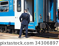 Train conductor next to a railway carriage 34306897
