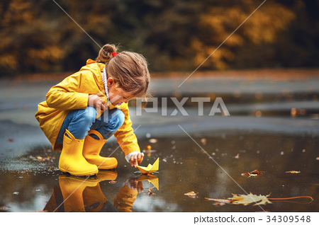 happy child girl  and paper boat in   puddle  34309548
