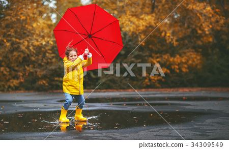 happy child girl with an umbrella   in puddle    34309549
