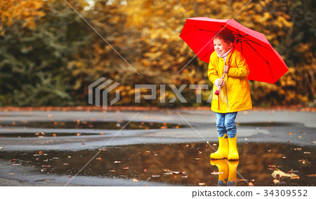 happy child girl with an umbrella  in puddle    34309552