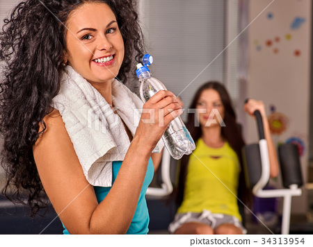 Woman in gym workout fitness equipment. Girl drink 34313954