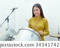 Young Asian teenage girl plays the drums in studio 34341742