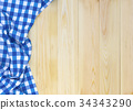 Bule and white checkered fabric on wooden table. 34343290