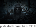 Human skull in jacket with fence over dead tree 34352910
