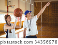 Male coach advising female basketball player 34356978