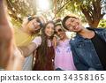 Portrait of smiling friends against trees 34358165