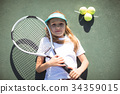 Portrait of tennis player lying on court 34359015