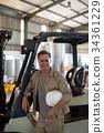 Portrait of happy worker standing near forklift 34361229