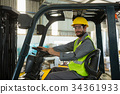 Smiling worker driving a forklift car in factory 34361933