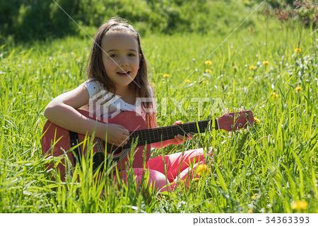 Portrait of cute girl playing guitar in field 34363393