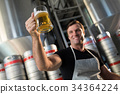 Low angle view of smiling worker holding beer glass 34364224