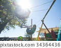 Siblings swinging against sky during sunny day 34364436
