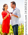 Smiling young couple toasting red wine 34365621