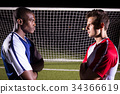 Side view of young male soccer players looking at each other 34366619