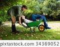 Man interacting with woman while pushing wheelbarrow in garden 34369052