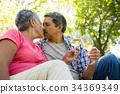 Senior couple kissing while drinking wine 34369349