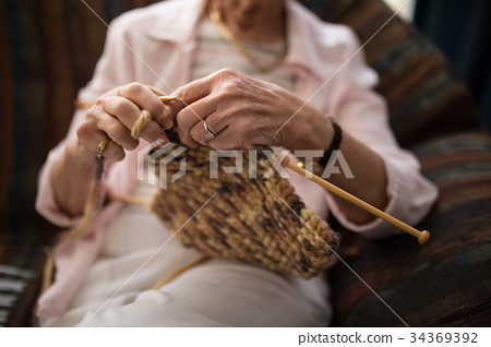 Midsection of senior woman knitting wool while sitting on sofa 34369392