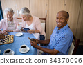 Smiling senior man using mobile phone while having tea with friends 34370096