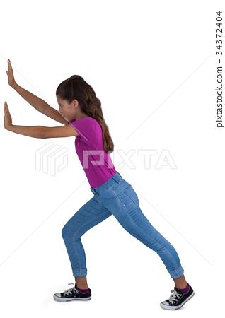 Girl pushing against white background 34372404