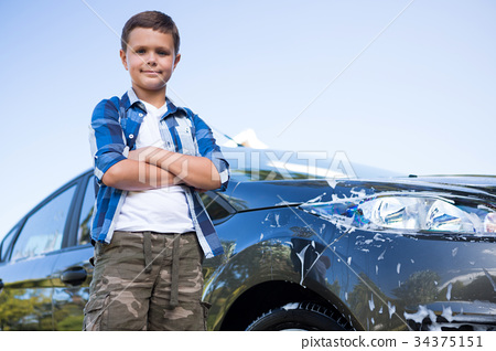 Teenage Boy Standing With Arms Crossed Near A Car Stock