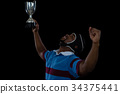 Happy rugby player holding trophy 34375441