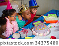 Boy blowing candles on cake 34375480