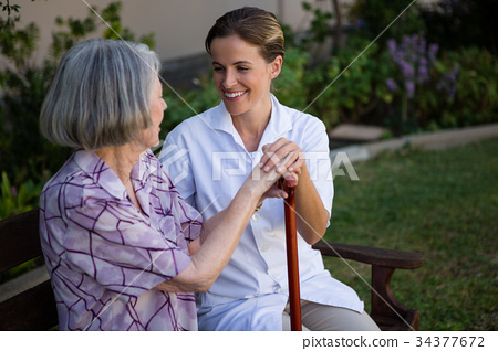 Woman talking to doctor while sitting on bench at park 34377672
