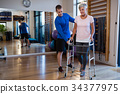 Physiotherapist assisting senior woman patient to walk with walking frame 34377975