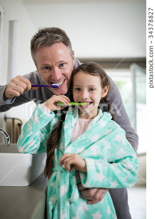 Smiling father and daughter brushing teeth in bathroom 34378827
