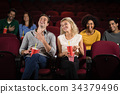 Couple watching movie in theatre 34379496