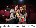 Couple watching movie in theatre 34380252
