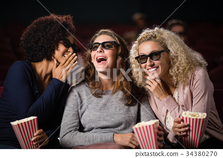 Female friends gossiping while watching movie 34380270