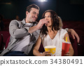 Couple watching movie in theatre 34380491