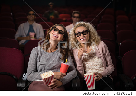 Female friends watching movie in theatre 34380511