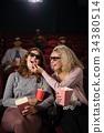 Female friends watching movie in theatre 34380514