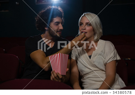 Couple having popcorn while watching movie in theatre 34380578
