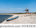 Blue rowing boat and an old windmill by seaside 34383836